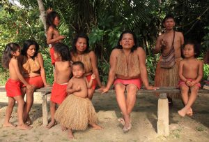 Family of indigenous people in straw and red clothes