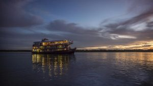 Amazon riverboat sailing at night with lights and sunset
